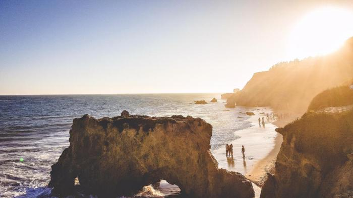 People walk along El Matador Beach, Malibu, Calif. | Photograph by Joseph Bautista, Getty Images